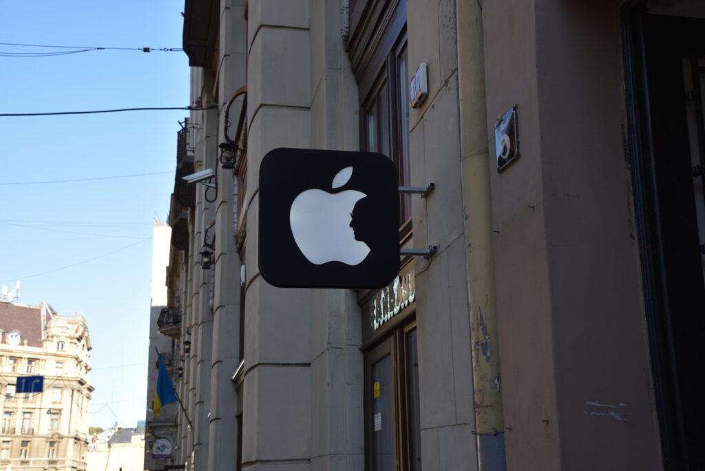 Szyld sklepu Aplle a na nim zarys twarzy - Steve Jobs, nadgryzione jabłko