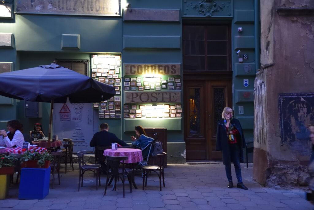 City break we Lwowie, Lwów, kobieta rozmawia przez telefon przed fasadą lokalu Poczta na Drukarskiej
