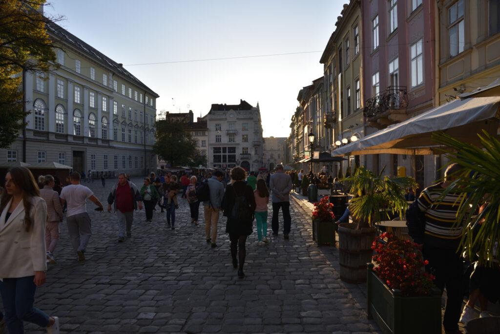 Na lwowskim rynku tuż przed zachodem słońca, półmrok, ludzie, stoliki