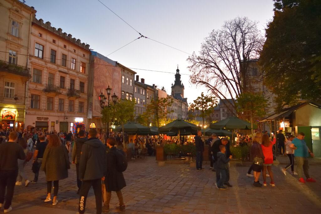 Stare miasto we Lwowie - rynek chwilę po zachodzie słońca, półmrok, ludzie, parasole