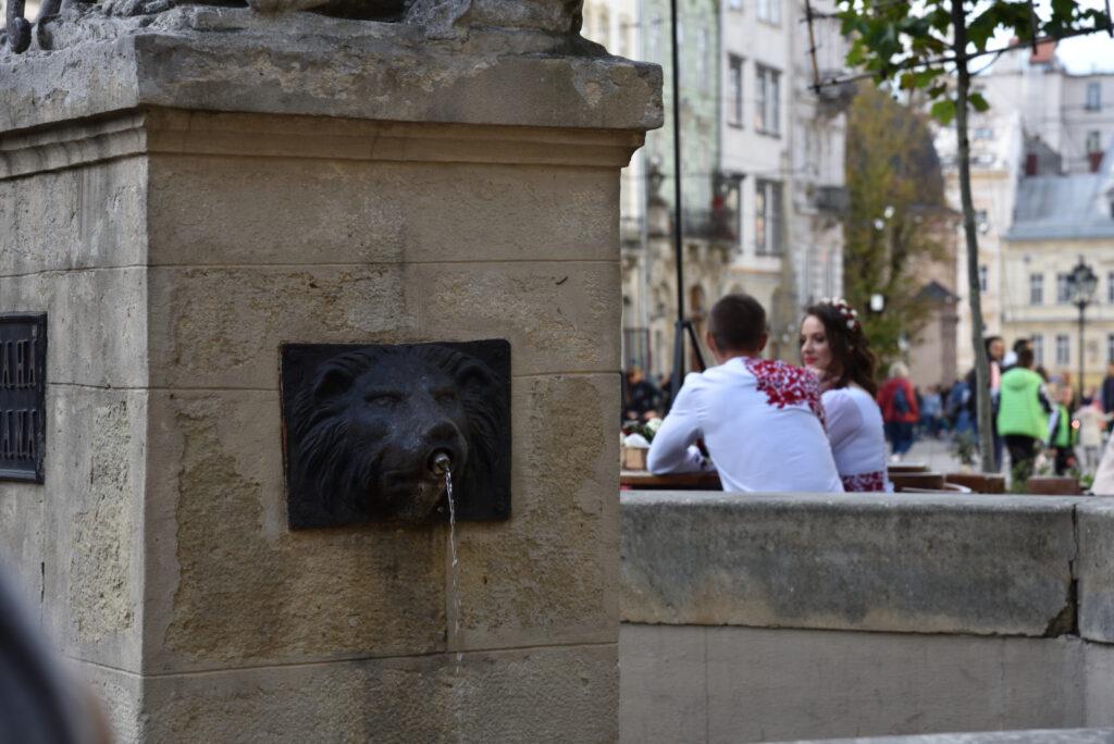 Stare miasto we Lwowie - w tle młoda para, na pierwszym planie fonanna