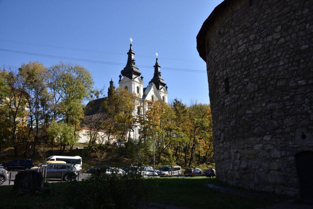 Na pierwszym planie fragment baszty prochowej a w tle klasztor karmelitów bosych we Lwowie
