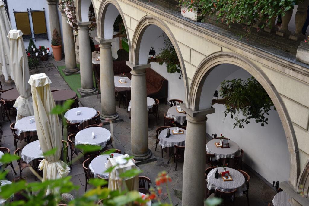 Stoliki restauracyjne na Włoskim Podwórku we Lwowie, stoliki nakryte białymi obrusami